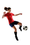 Female Soccer Player Kicking Ball. Portrait of female soccer player kicking ball isolated over white background stock images