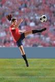 Female Soccer Player Kicking Ball stock image