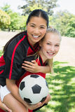 Female soccer player piggybacking teammate. Portrait of happy female soccer player piggybacking teammate at park Royalty Free Stock Photography