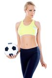 Female soccer player posing with ball Royalty Free Stock Image