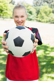 Female soccer player showing ball at park Stock Images