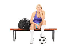 Female soccer player sitting on a bench Royalty Free Stock Photos