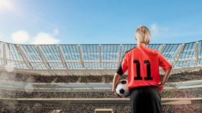 Female soccer player standing with the ball against the crowded stadium on background stock photos