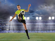 Female Soccer Player. Young female soccer player playing inside stadium at dusk stock photo