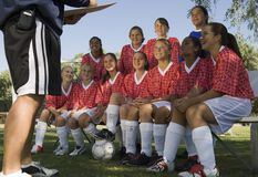 Female Soccer Players Listening To Coach. Group of multiracial female soccer players listening to coach on field Royalty Free Stock Photo