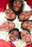 Female soccer team forming huddle. Directly below shot of happy female soccer team forming huddle Royalty Free Stock Photo
