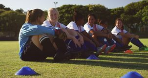 Female soccer team sitting on the ground while talking on soccer field. 4k. Front view of happy diverse female soccer team sitting on the ground while talking stock footage