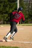 Female Softball Player. First base runner wearing black pin stripe pants and a maroon shirt stock photos