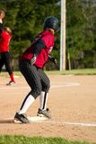 Female Softball Player. First base runner wearing black pin stripe pants and a maroon shirt stock images