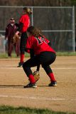 Female Softball Player. First baseman wearing black pants and a red shirt royalty free stock photo