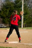 Female Softball Player. First baseman wearing black pants and a red shirt royalty free stock image