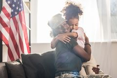 Female soldier in camouflage clothes and her daughter embracing. On sofa royalty free stock images