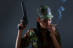 Female soldier in camouflage uniform with gun and cigar. Smoke royalty free stock images