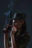 Female soldier in camouflage uniform with gun and cigar Stock Photography