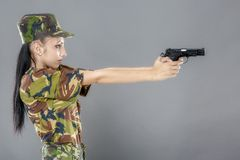 Female soldier in camouflage uniform with weapon Stock Photo