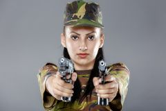 Female soldier in camouflage uniform with weapon. Isolated on gray background Royalty Free Stock Photography
