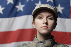 Female soldier in front of US flag. Looking at camera, horizontal shot stock photo