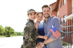 Female soldier with her family outdoors. Military service. Female soldier with her family and American flag outdoors. Military service royalty free stock photography