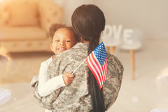 Female soldier hugging her daughter holding a flag. Proud American. Loving brunette mother hugging her cute little curly daughter while she holding the American stock photography
