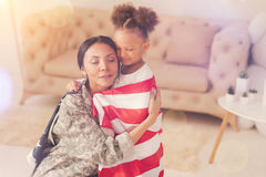 Female soldier hugging her daughter wrapped in American flag. My love. Affectionate young mother in a military uniform hugging her daughter while they both being stock photos