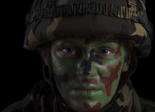 Female Soldier Face. Female Soldier in a Marine Helmet With Face Camouflage Against Dark Background Stock Photography