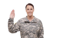 Female soldier performing oath. Smiling female soldier holding up right hand royalty free stock photo