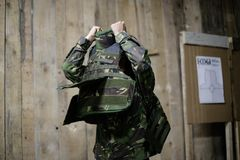 Female bulletproof vest. A female soldier puts on a bulletproof military vest Royalty Free Stock Photos