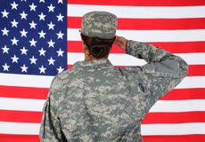 Female Soldier Saluting Flag. Closeup of an American Female Soldier in combat uniform saluting a flag. Seen from behind horizontal format with the flag filling Royalty Free Stock Photo