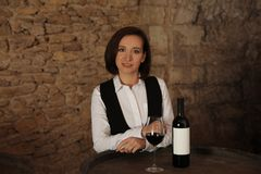 Female sommelier with glass and bottle of red wine. At table indoors Stock Images