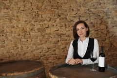 Female sommelier with glass and bottle of red wine. At table indoors royalty free stock image