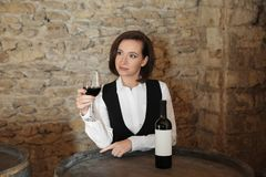 Female sommelier with glass of red wine. At table indoors royalty free stock photo