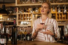 Smart nice woman holding a wine glass in her hand. Female sommelier. Smart nice woman holding a wine glass while working as a sommelier in the restaurant royalty free stock photo