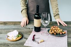 Female sommelier standing near table with wine. And food stock image