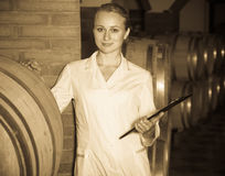 Female sommelier in wine cellar. Portrait of cheerful professional taster of winery posing with wine in cellar Stock Photo