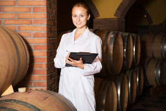 Female sommelier in wine cellar. Portrait of glad professional taster of winery posing with wine in cellar Royalty Free Stock Images