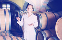 Female sommelier in wine cellar. Professional taster of winery posing with wine in cellar Royalty Free Stock Photo