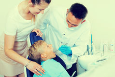 Female with son are visiting dentist. In dental office Stock Photography