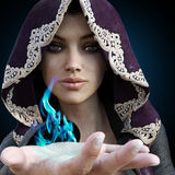 Female sorcerer with blue magic coming from her hand. On a gradient black background Royalty Free Stock Photography