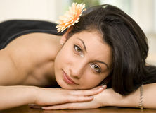 Female in spa or massage. Young beautiful female lying on massage bed in spa with relaxed expression Stock Photos