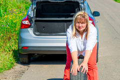 Female spare wheel rolls on the road Stock Photos