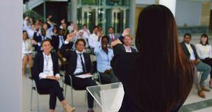 Female speaker speaks in a business seminar 4k. Rear view of Asian female speaker speaks in a business seminar. Business people raising their hands in a seminar stock footage