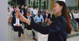Female speaker speaks in a business seminar 4k. Rear view of Asian female speaker speaks in a business seminar. Business people listening to her 4k stock footage