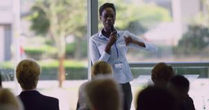 Female speaker speaks in a business seminar at modern office 4k. Front view of African American female speaker speaks in a business seminar at modern office stock footage