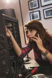 Woman fixing computer. Female IT specialist putting together components of a computer case while having a phone conversation stock images