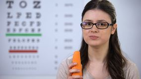 Female in spectacles eating fresh carrot, eyesight care, vitamins and minerals. Stock footage stock video