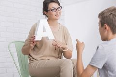 Female speech therapist showing letter. Young positive female speech and language therapist showing a letter to little boy during therapy session Royalty Free Stock Images