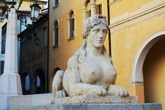 Female sphinx, in Conegliano Veneto, Treviso, Italy. Female sphinx statue,cityscape and the Accademy Theatre, in Piazza Cima, in Conegliano Veneto, Treviso Royalty Free Stock Photo