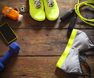 Female sport equipment on a wooden background. Sports items: sneakers, clothing, bottle of smoothie,  dumbbell and mobile phone on the wooden background. Set Royalty Free Stock Images