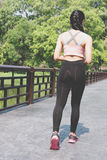 Female sport fitness runner jogging outdoors on bridge in spring. Female sport fitness athlete runner jogging outdoors on bridge in spring or summer. Healthy Stock Photography