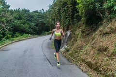 Female sport model running on road in mountains. Fitness woman training outdoors. royalty free stock image